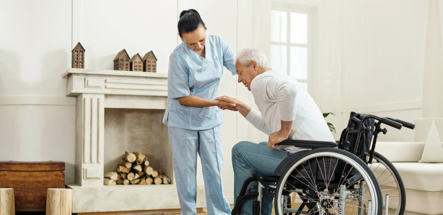 caregiver assisting senior man to get up on the wheelchair
