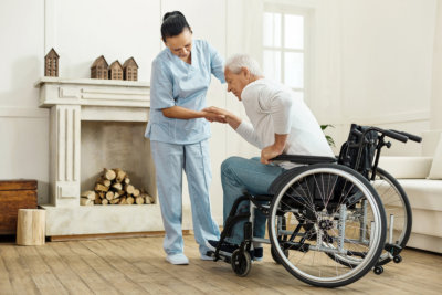 lady caregiver helping senior man to get up from the wheelchair