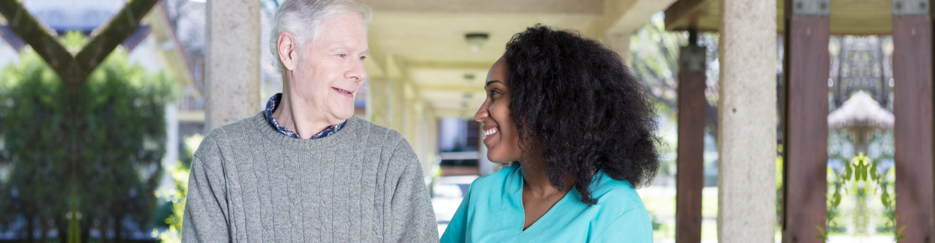 caregiver and elderly man looking at each other